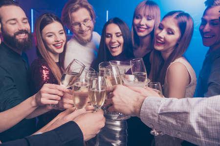 Beschnittenes Nahaufnahmeporträt von netten, schicken, bezaubernden, glamourösen Luxus, attraktiven modischen, wunderschönen, fröhlichen Damen und Jungs, die Spaß haben, Weingläser zu klirren, funkeln im Nachtclub mit Nebellicht Standard-Bild