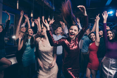 Nice-looking attractive glamorous cheerful glad positive stylish chic ladies and gentlemen having fun free time weekend solemn festal festive fest feast in fashionable luxury place nightclub indoors