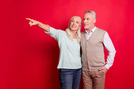 Close up photo beautiful she her he him his aged guy lady partners couple indicate fingers empty space sale discount foreign shopping wear sweater shirt waistcoat isolated red burgundy background