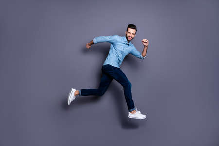 Full length body size view portrait of his he nice cool perfect strong content cheerful cheery macho guy running activity marathon isolated over gray violet purple pastel background Stock Photo
