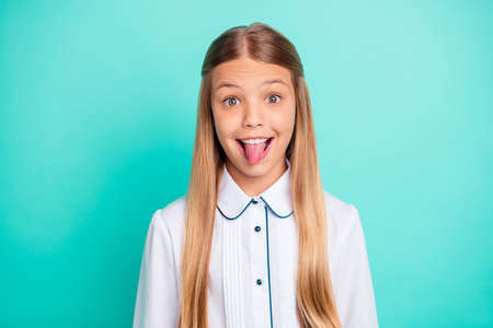Close-up portrait of nice-looking attractive lovely winsome charming girlish funny cheerful cheery crazy pre-teen girl showing tongue out isolated on bright vivid shine blue green turquoise background