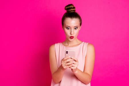 Portrait cute astonihsed person people she her hold hand moderrn technology relax impressed wonder incredible information unbelievable unexpected outfit top knot isolated colorful pink background