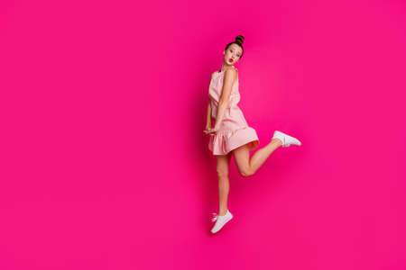 Full length body size view photo of lovely sweet attractive lady have free time dressed top-knot pomade lipstick red active motion movement legs sneakers isolated pink background