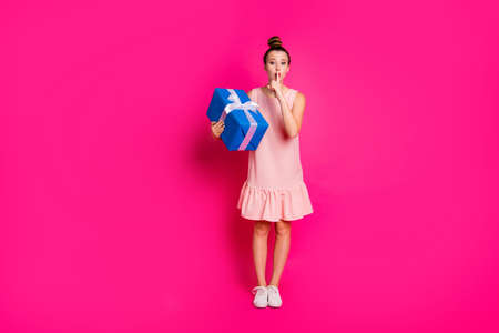 Full length body size view photo charming youth millennial celebration want give blue box anniversary 8-march ask dont share private information shh dress she her top-knot isolated pink background 版權商用圖片