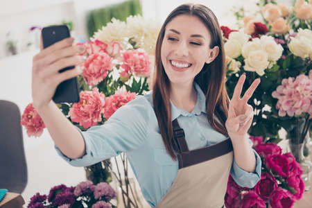 Close up photo of cute attractive friendly youth make photo camera video call live small business retail variety entrepreneur make v-signs free time rest relax content enjoy orangery blue shirt Stock fotó