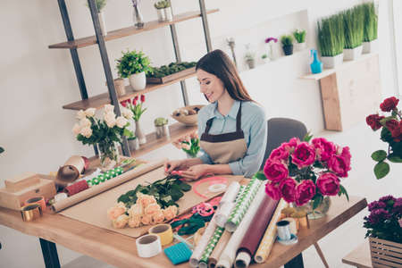 Portrait of charming lovely lady people touch hand s flora florist floral nature environment satisfied content sit table desk make process art create blue shirt greenhouse