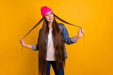Close up photo beautiful amazing she her stylish lady teen playing very long curls weekend vacation day off street perfect look wear casual jeans denim jacket pink hat isolated yellow background