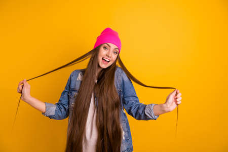 Close up photo beautiful amazing she her stylish lady friendly teen playing very long curls weekend vacation day off mood wear casual jeans denim jacket pink hat isolated yellow background