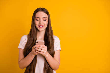 Close up photo beautiful amazing she her lady very long hairstyle wondered hold hands arms telephone read romantic letters boyfriend wear casual pastel t-shirt isolated yellow bright background