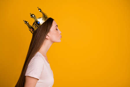 Close up side profile photo beautiful she her lady leader gold crown head coronation nomination special social status send air kisses citizens wear casual pastel t-shirt isolated yellow background Фото со стока