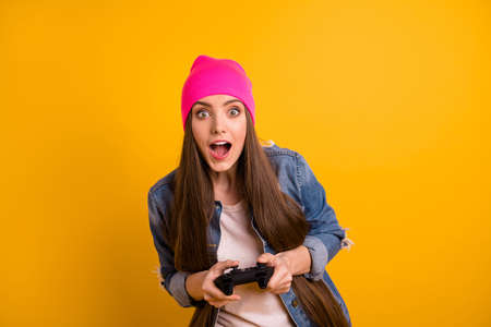 Close up photo beautiful she her lady very long hairstyle hands arms joystick favorite video game open mouth win winner victory wear casual jeans denim jacket pink hat isolated yellow background