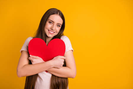 Close up photo beautiful lady very long hair hold hands arms big large paper heart postcard invitation boyfriend husband romance date prom wear casual t-shirt isolated yellow background Stock fotó