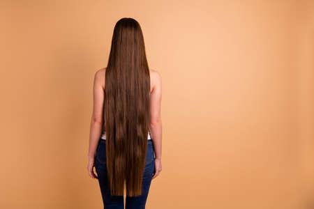 Zamknij się z tyłu z tyłu za widok zdjęcie piękne niesamowite jej pani bardzo długie brązowe włosy pokazujące świetny stan każdy lok nosić dorywczo biały podkoszulek dżinsy denim na białym tle pastelowe beżowe tło Zdjęcie Seryjne