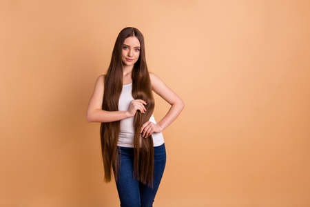 Close up photo beautiful amazing her she lady hold arms very long brown hair great condition curls show results after lamination wear casual white tank-top jeans denim isolated pastel beige background