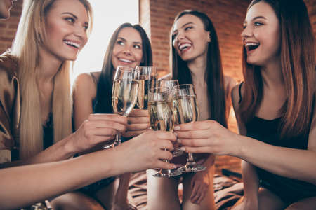 Cropped close up photo five amazing beautiful she her ladies hands arms glasses festive golden beverage short nightie sit sheets clink listen tell talk toasts sleep costumes girls night room indoors