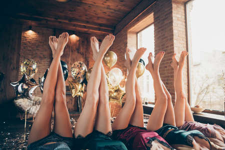 Cropped nice crossed well-groomed legs attractive lovely fascinating luxurious feminine ladies lying on bed festal celebratory preparation in loft industrial style interior room house