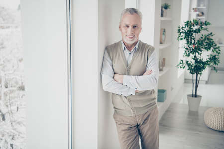 Close up photo amazing manager he him his aged man arms crossed bossy chief look self-confident wear white shirt waistcoat pants stand lean window comfort bright flat house living room indoors