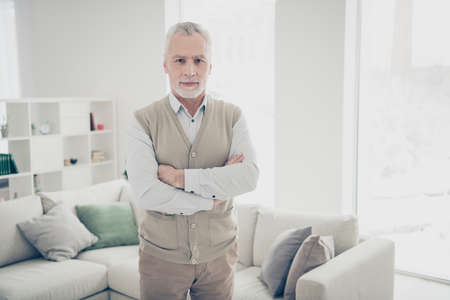 Close up photo amazing manager he him his aged man arms crossed bossy chief look, self-confident wear white shirt waistcoat pants stand near cozy comfort divan bright flat house living room indoors