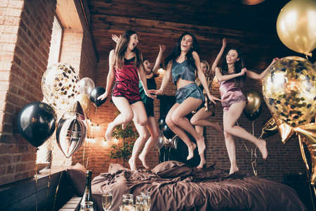 Low below angle full length body size view of nice attractive slim fit adorable cheerful crazy group having fun great free time in hostel loft industrial style interior room house indoors Archivio Fotografico