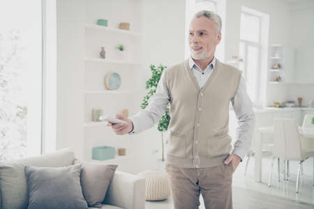 Close up photo amazing he him his aged man arms hands behind head console change mode system turn on cooling regime wear white shirt waistcoat pants comfy bright flat house living room indoors