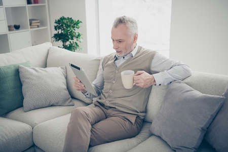 Close up side profile photo amazing he him his aged man hands arms hot beverage e-reader information book adventure novel wear white shirt waistcoat pants sit cozy divan flat house living room indoors Reklamní fotografie
