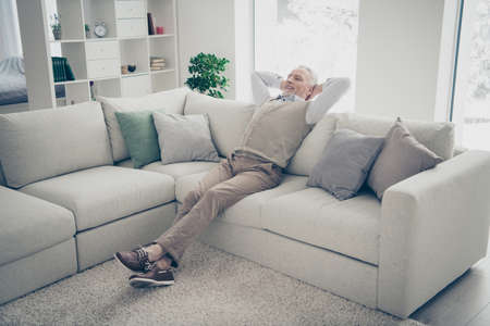 Full length body size photo amazing he him his aged man overjoyed calm hands arms behind head day off imaginary flight wear white shirt waistcoat pants sit cozy divan flat house living room indoors Archivio Fotografico