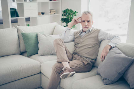 Close up photo amazing he him his aged man inspiration calm peaceful kindhearted easy-going serious look wear white shirt waistcoat pants sit cozy comfort divan bright flat house living room indoors Reklamní fotografie