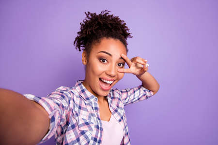 Close up photo nice charming satisfied millennial make v-sign eyes scream content enjoy rejoice photo travel summer checked trendy stylish top knot shirt isolated purple background free time concept