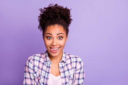 Close up photo of careless cute lovely teen teenager top-knot have free time holidays weekends foolish make faces enjoy rejoice dressed checked shirt isolated on purple background