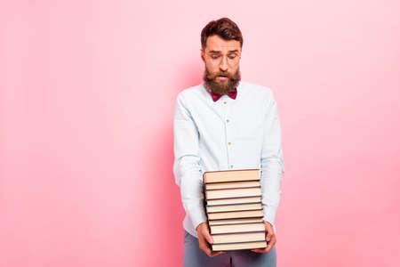 Photo of crying frustrated guy holding heavy stack of books in hands isolated pastel background Фото со стока