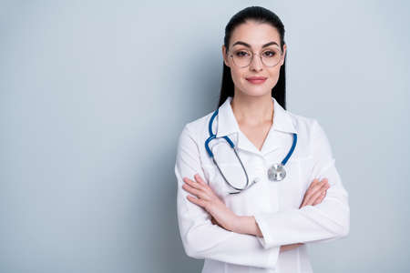 Close up photo beautiful amazing lady young doctor first working day hospital ready begin start crossed arms friendly wear phonendoscope white science costume specs isolated grey background Stock Photo