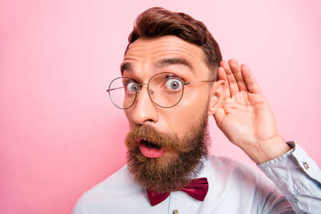 Close up portrait of funny funky loony geek astonished hipster holding palm near ear isolated pastel background Foto de archivo
