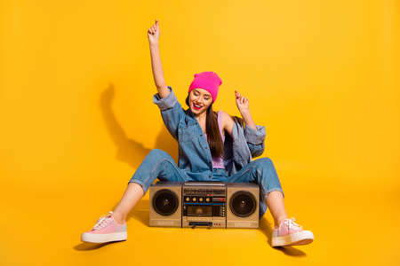 Full length body size photo beautiful she her lady enjoy weekend vacation vintage audio recorder sit floor motion wear casual jeans denim jacket shoes pink hat isolated yellow vivid bright background Фото со стока