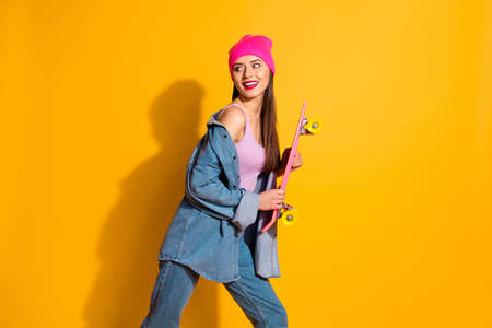 Close up side profile photo beautiful she her lady hands arms skate board glossy pomade look empty space sportive person wear casual jeans denim jacket tank-top pink hat isolated yellow background