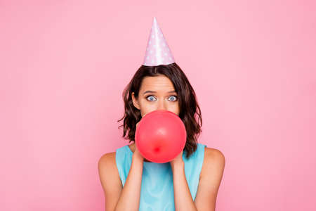 Close up photo amazing beautiful she her lady attractive appearance birthday cap head hide half face big red balloon blowing air staring wear shiny colorful blue dress isolated pink bright background
