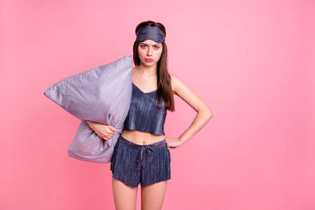 Portrait of her she nice-looking shine attractive lovely perfect stunning mad grumpy straight-haired teenage girl standing wakeup holding pillow isolated over pink background