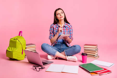 Full length body size photo beautiful she her sit floor notebook ponder pensive hands planner noting surround learn stuff wear casual checkered plaid shirt jeans denim isolated pink background