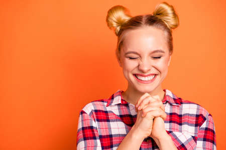 Close up photo attractive nice she her lady perfect appearance fingers crossed eyes closed wait cheerleader fan asking team win wear casual checkered plaid pink shirt isolated bright orange background