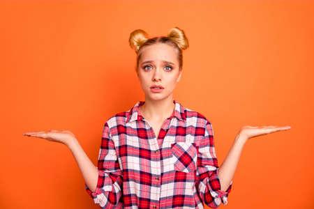 Close-up foto mooie angst dat ze haar dame perfect uiterlijk houdt open handen armen producten niet zeker welke gebruik selecteren kiezen slijtage casual geruit geruite roze shirt geïsoleerd fel oranje achtergrond