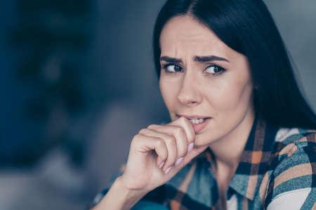 Close-up zijprofielfoto zij haar dame ontevreden hopeloos arm hand bijten vingers zenuwen gemaakt fout twijfelen vertellen of niet dragen geruit geruit hemd zitten mager divan plat huis woonkamer binnenshuis