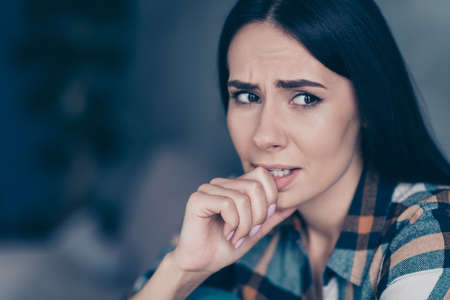 Nahaufnahme seitliches Profilfoto sie ihre Dame unzufrieden hoffnungslos Arm Hand beißen Finger Nerven haben Fehler gemacht Zweifel haben oder nicht tragen kariertes kariertes Hemd sitzen mageres Diwan flaches Haus Wohnzimmer drinnen