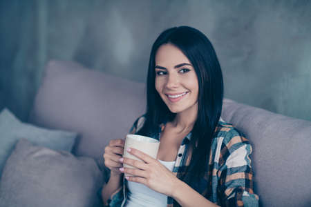 Close up side profile photo beautiful she her lady hands arms hot warm beverage wondered imaginary flight calm peaceful kindhearted wear checkered shirt sit cozy divan house living room indoors