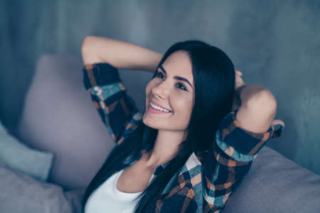 Close up side profile photo beautiful she her lady hands arms behind head imaginary flight calm peaceful kindhearted perfect teeth wear checkered shirt sit cozy divan house living room indoors Reklamní fotografie