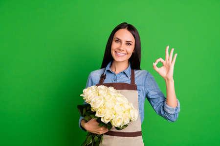 Portret charmante aantrekkelijke mooie dame assistent verkoper ondernemer advertenties advertentie keuze besluit promo product plantkunde milieu rozeknop shirt blauwe denim jeans geïsoleerde groene achtergrond Stockfoto