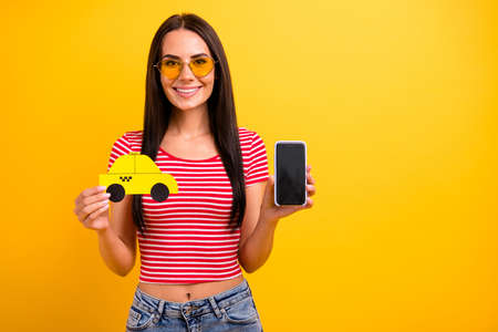 Portrait charming student lady weekend hold hand paper card taxi touch screen isolated leisure long haircut trendy eyeglasses eyewear yellow background denim jeans red striped stylish t-shirt she her