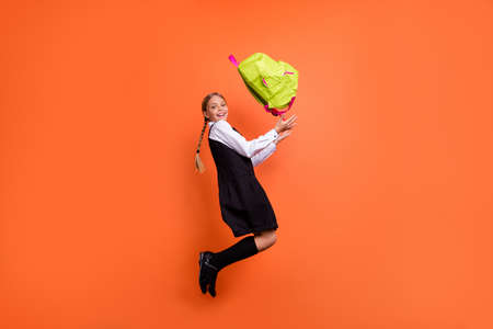 Full length body size profile side view of nice attractive cheerful careless pre-teen girl having fun active motion movement throwing up green bag isolated on bright vivid shine orange background 스톡 콘텐츠