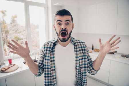 Portrait of his he nice attractive mad furious devastated bearded guy screaming in modern light white interior style kitchen
