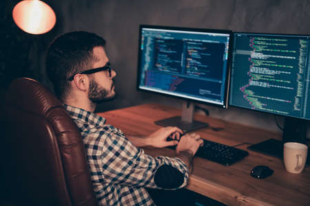 Close up side profile photo handsome he him his guy coder typing php css keyboard development outsource IT processing language two monitors table office agency wear specs formalwear plaid shirt