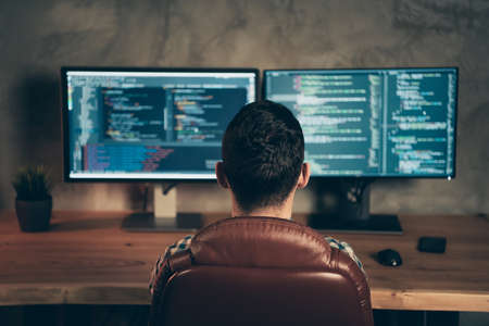 Tył z tyłu za widok brunet facet profesjonalny ekspert specjalista siedzący przed ekranem tworząc projekt strony internetowej na drewnianym przemysłowym wnętrzu stanowiska pracy Zdjęcie Seryjne