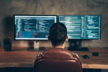 Vista posterior detrás de la vista del especialista experto profesional brunet guy sentado frente a la pantalla creando un diseño de sitio web en la estación de lugar de trabajo interior industrial de madera Foto de archivo